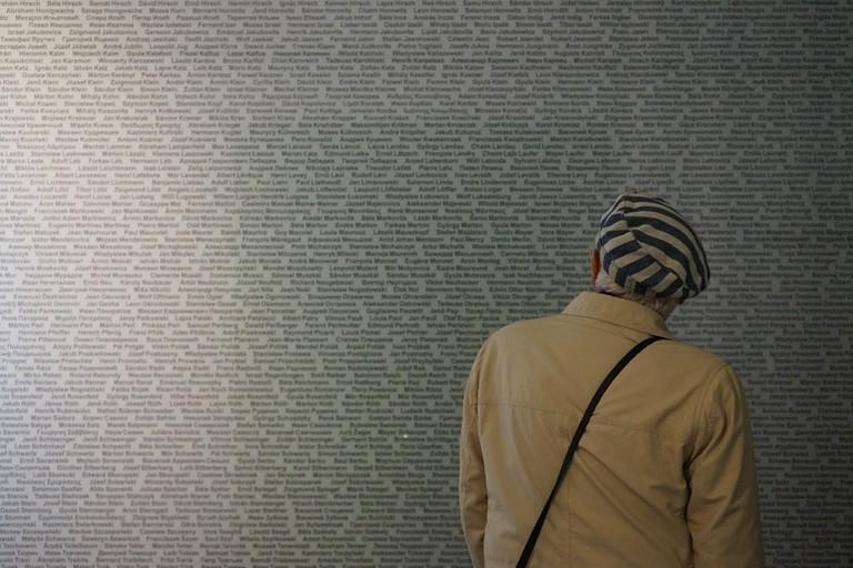 Ein ehemaliger polnischer Häftling vor der Wand der Namen and der Gedenkstätte Melk (© Christian Rabl).