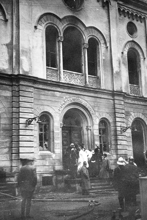 Die ausgebrannte Synagoge mit Schaulustigen und Feuerwehrleuten. Die Feuerwehr ist zwar beim Brand anwesend, sorgt aber nur dafür, dass das Feuer nicht auf benachbarte Gebäude übergreift. (Bildnachweis: Archiv der Stadt Linz)
